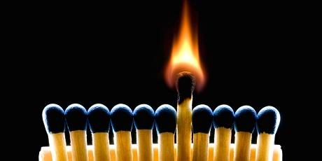 Many dark blue matches on a black background (one match burns).