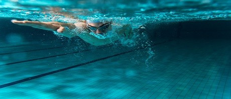 Male swimmer swimming underwater in a pool